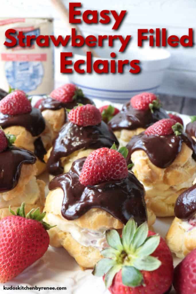 Closeup title text image of strawberry filled eclairs with chocolate ganache topping and fresh strawberry garnish.