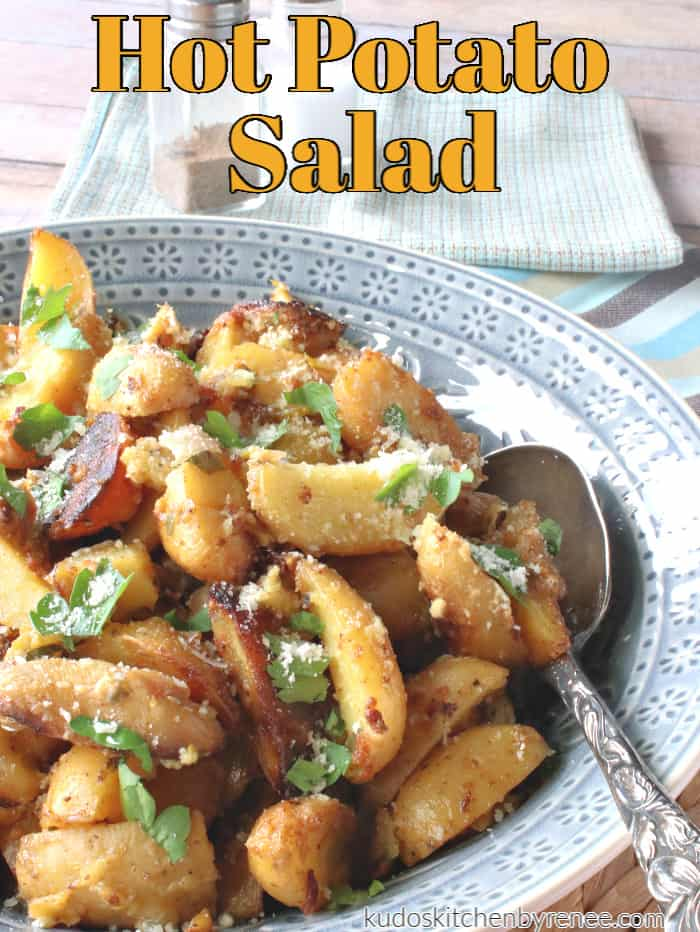 A vertical closeup photo of hot potato salad in a blue bowl with Parmesan cheese and parsley.