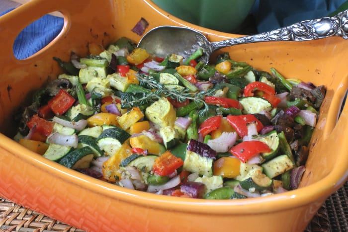 An orange roasting pan filled with colorful roasted summer vegetable medley with a serving spoon