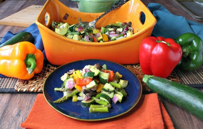 A plate of roasted summer vegetables on a blue plate with a casserole dish in the background.
