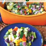 A round blue plate with roasted summer vegetable medley along with an orange casserole dish in the background.