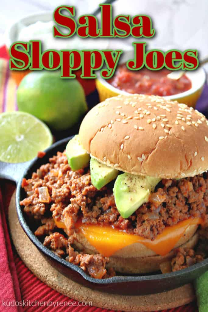 Closeup vertical image of a salsa sloppy joes sandwich in a cast iron skillet with melted cheese and avocado slices on a bun.