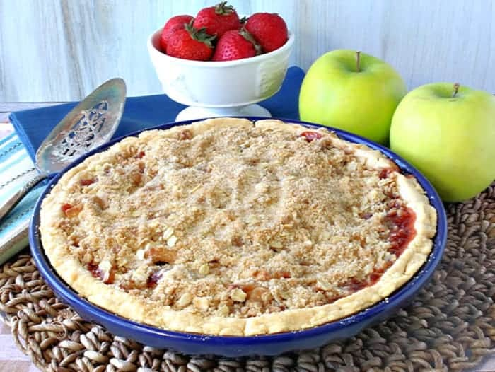 A strawberry apple pie with a streusel topping with a dish of strawberries and 2 apples in the background.