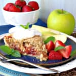 A slice of strawberry apple pie on a blue plate with apple slices and fresh strawberries, mint, and whipped cream.