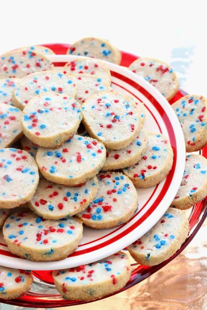 A vertical closeup of a two tiered cookie plate filled with cream cheese cookies with red, white, and blue sprinkles.