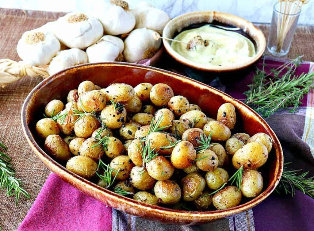 A brown oval bowl filled with baby roasted potatoes with garlic and herbs and a dipping sauce in the background.