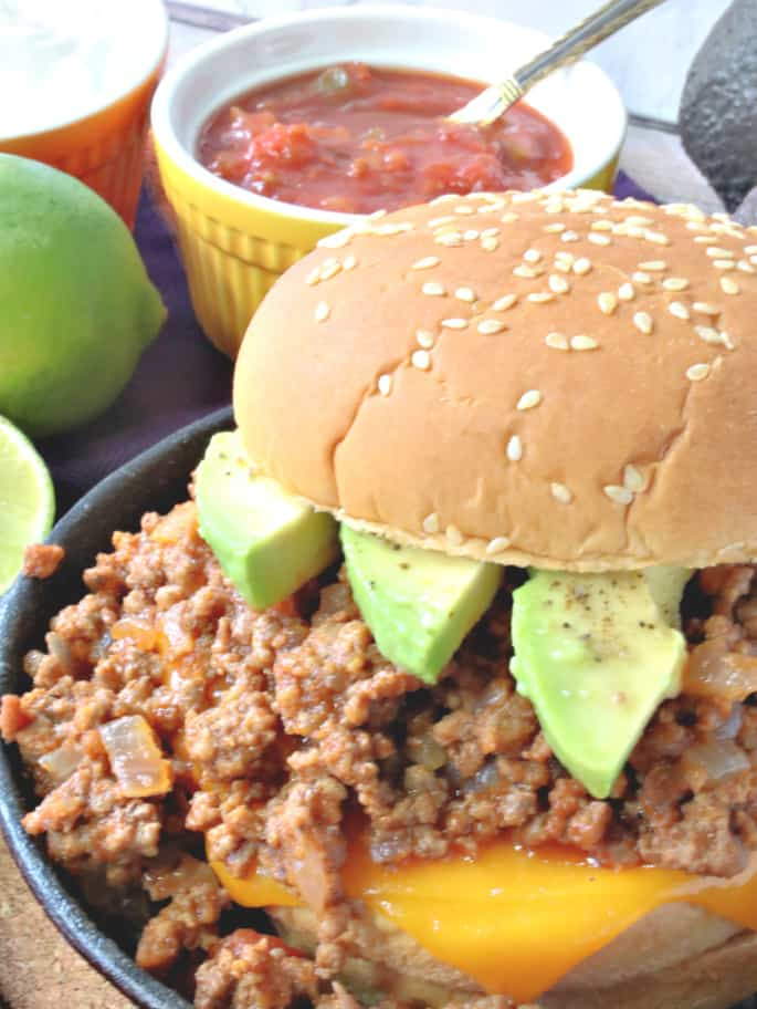 A closeup vertical image of a salsa sloppy joes on a sesame seed bun with limes and salsa in the background.