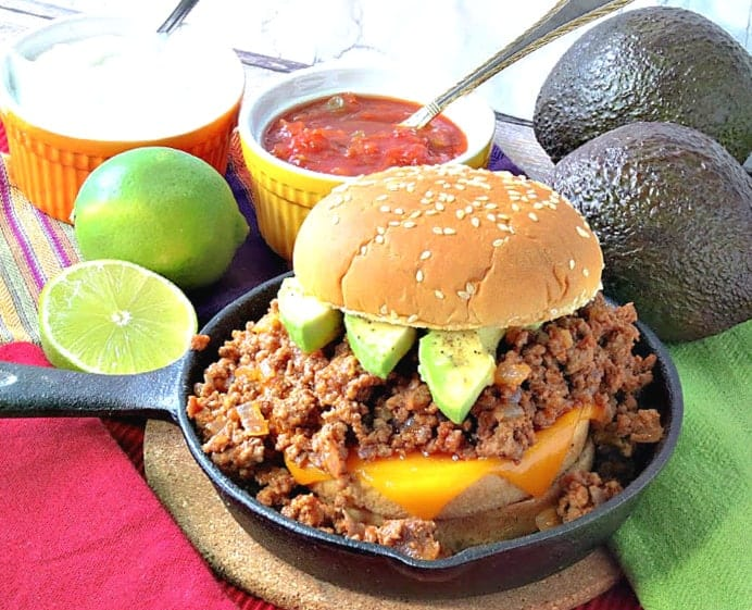 A salsa sloppy joes sandwich in a small cast iron skillet with limes, avocados, salsa, and sour cream in the background.