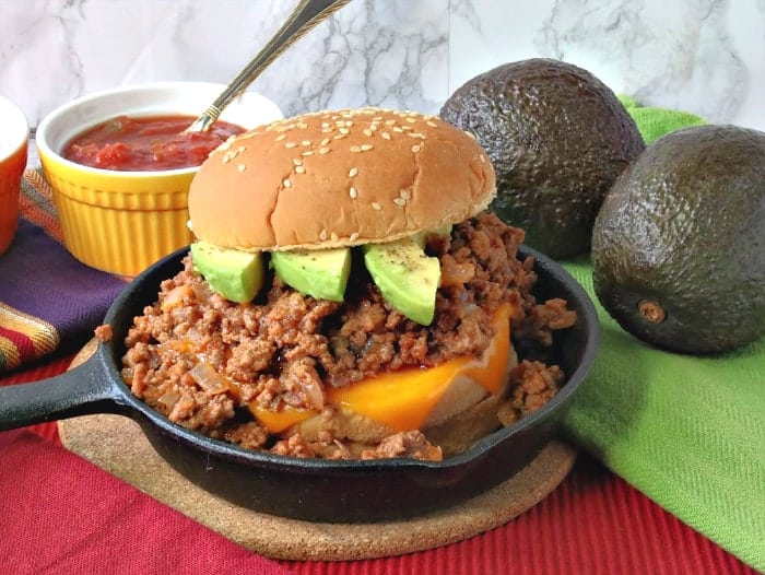 A salsa sloppy joe sandwich in a small cast iron skillet with avocado slices and a sesame seed bun.