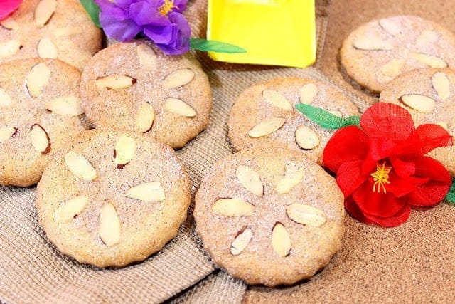 A pile of sand dollar cookies on a tan background with colorful flowers and a yellow plastic shovel.