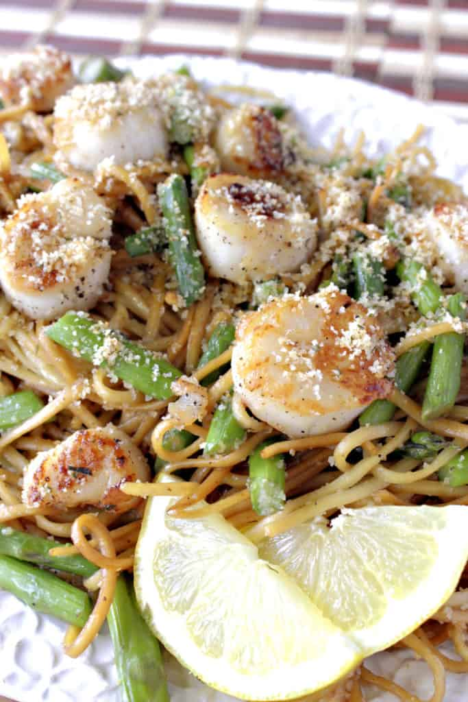 Closeup overhead vertical photo of seared scallops with linguine and asparagus on a platter with lemon slices and breadcrumbs.