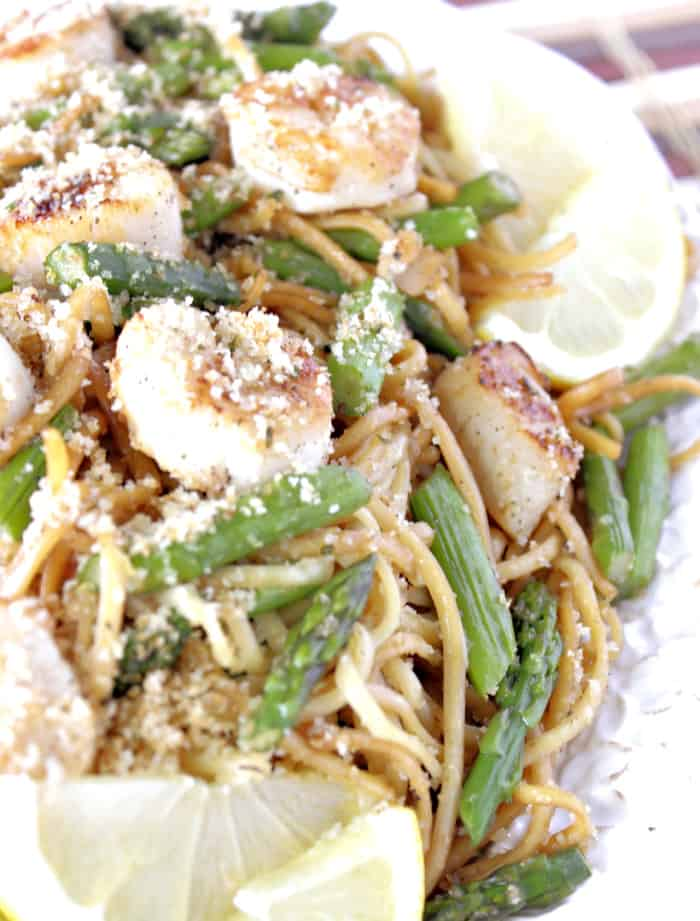Super closeup photo of seared scallops with linguine and asparagus on a platter with lemon and toasted breadcrumbs.