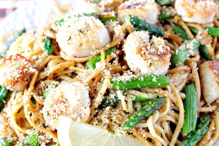 A closeup horizontal photo of Seared Scallops with Linguine and Asparagus with a lemon slice.