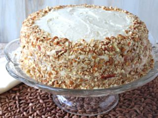 An entire banana poppy seed cake covered in pecans on a glass cake plate.