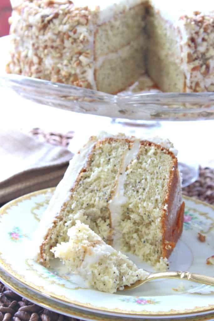 A vertical closeup of a slice of banana poppy seed cake on a pretty plate with the whole cake in the background.