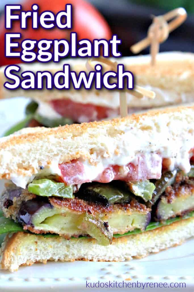 A vertical closeup of the inside of a fried eggplant sandwich with mayo, lettuce, and tomato and a title text graphic overlay. Fried Eggplant Sandwich recipe