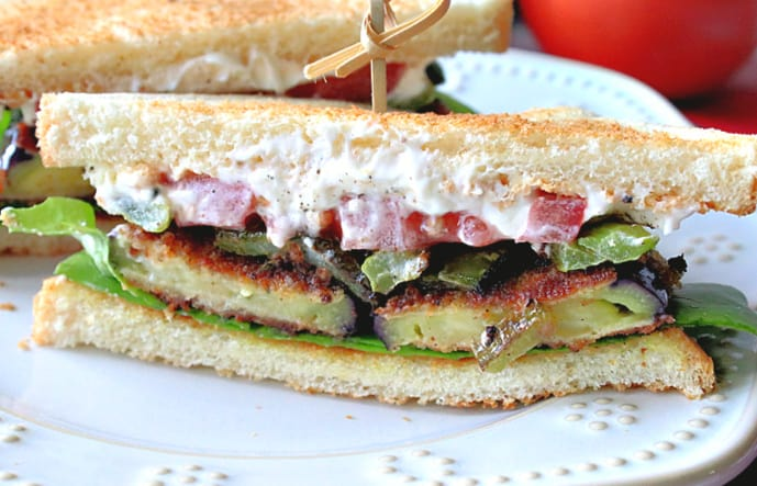 A super closeup of the inside of a fried eggplant sandwich with mayo, tomato, green pepper, and lettuce on a white plate with dots.