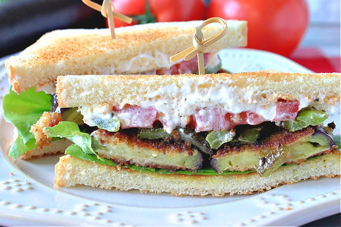 A closeup image of a fried eggplant sandwich cut in half, with a toothpick. How to make a fried eggplant sandwich with lettuce, tomato, and green bell pepper.
