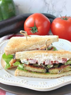 A fried eggplant sandwich on a white plate on a red and white tablecloth with a bell pepper, eggplant, and tomatoes in the background.
