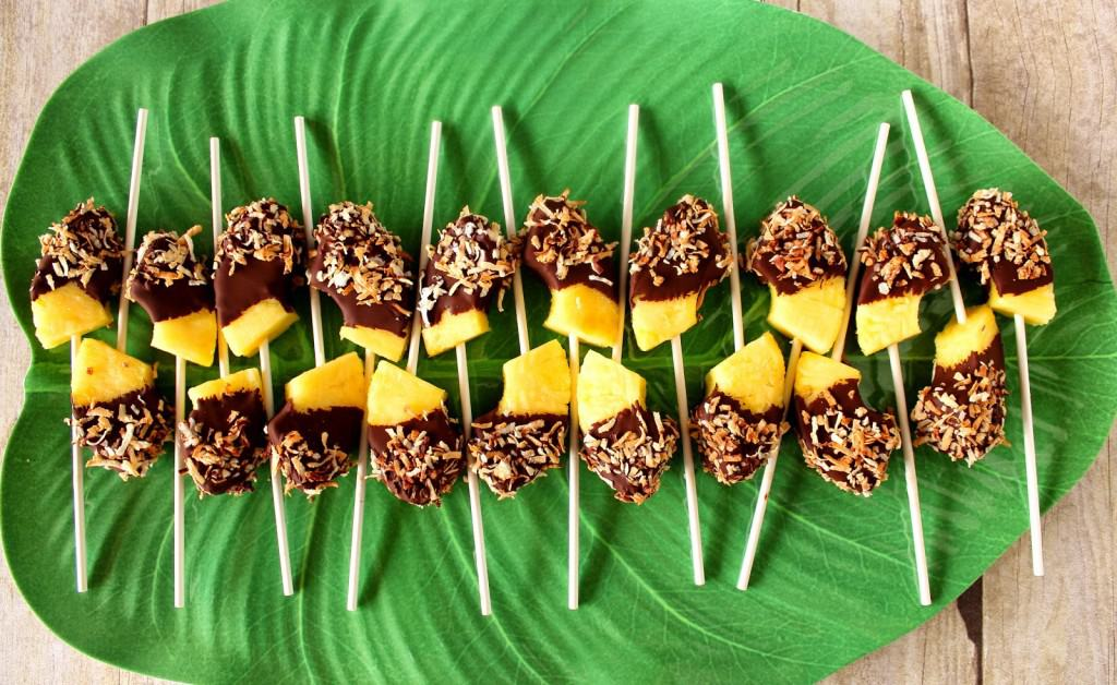 A tropical green leaf plate lined up with frozen pineapple pops with chocolate and toasted coconut.