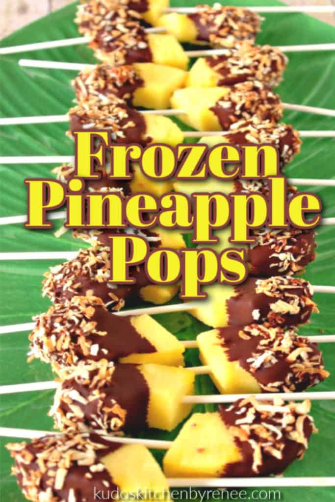 A row of frozen pineapple pops on a green platter with chocolate and coconut with title text overlay graphic