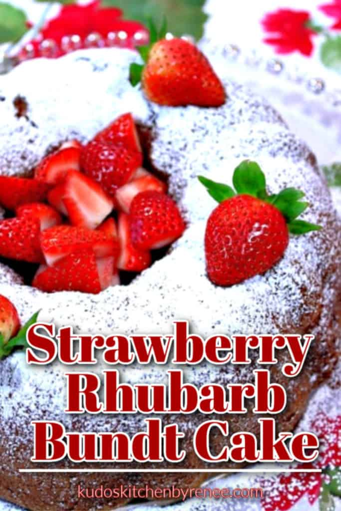 Closeup title text overlay image of a  strawberry rhubarb bundt cake with fresh strawberries is the middle and a confectioners sugar dusting on top.