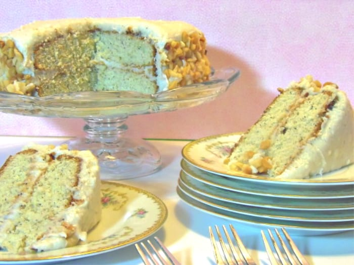 A banana poppy seed cake on a glass cake stand with two slices of cake on plates with a pink background.