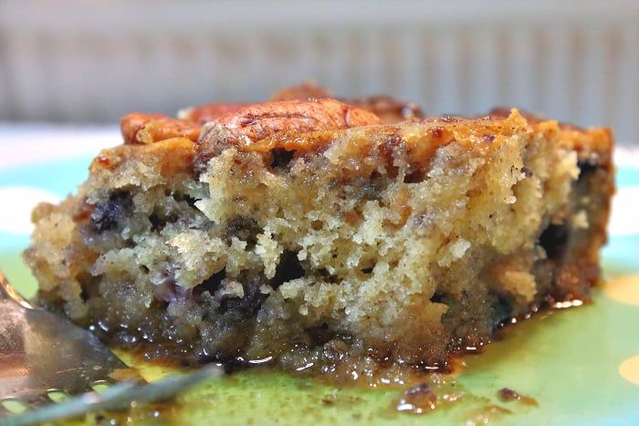 An extreme closeup of a slice of sausage blueberry breakfast casserole with a fork and maple syrup.