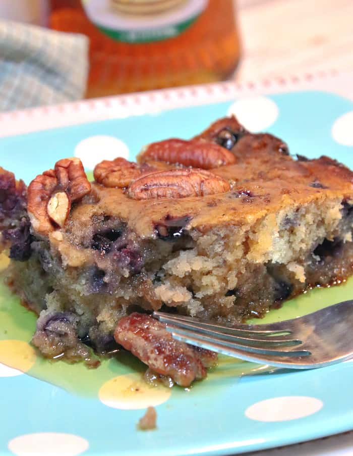 A closeup vertical image of a sausage blueberry breakfast casserole square on a blue polka dot plate with pecans and maple syrup.