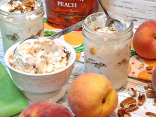A bowl and a couple of mason jars filled with no-churn peach and pecan ice cream with peaches on the side and pecans on the table