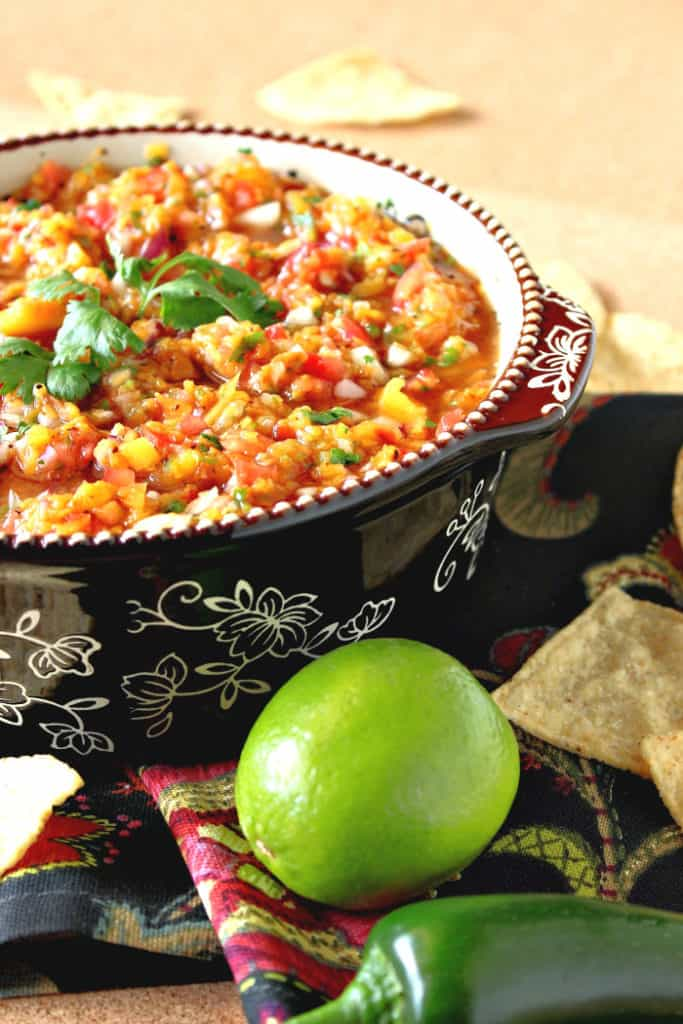 A vertical closeup photo of grilled peach salsa in a bowl with fresh cilantro and a lime and jalapeno pepper in the foreground.