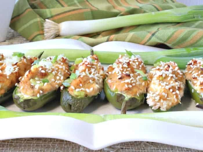 A closeup horizontal photo of jalapeno poppers stuffed with crab rangoon on a white rectangle platter topped with chopped scallions and a green and gold napkin in the background. How to make jalapeno poppers with crab rangoon filling