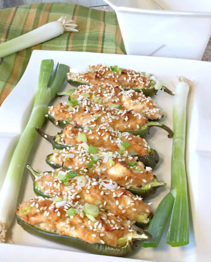 A closeup vertical photo of a white rectangle plate filled with jalapeno poppers stuffed with crab rangoon with scallions on the side of the plate.