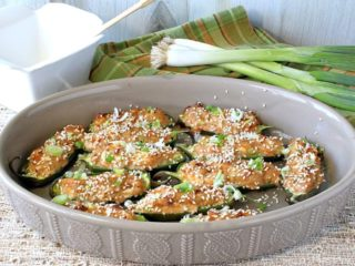 An oval tan dish filled with jalapeno poppers stuffed with crab rangoon and topped with chopped scallions