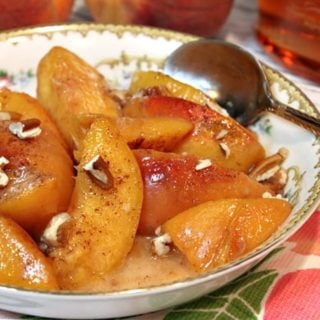 An offset photo of a bowl filled with peaches foster with chopped pecans over top.