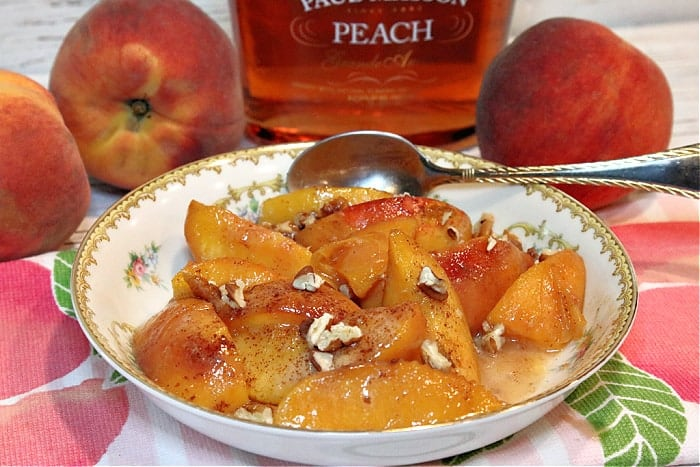 A pretty china bowl filled with peaches foster and topped with chopped pecans. Fresh peaches and peach brandy are in the background