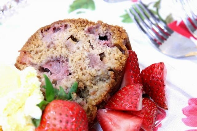 A closeup slice of strawberry rhubarb bundt cake on a plate with fresh strawberries and vanilla ice cream.