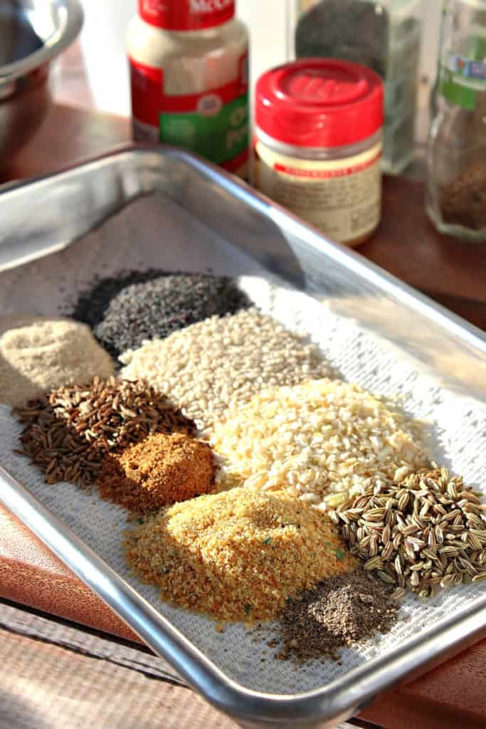 A vertical closeup image of a small baking tray filled with spices and seeds for homemade everything seasoning blend