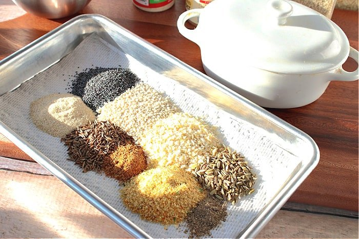 A small silver baking dish covered with piles of best homemade everything seasoning blend ingredients.