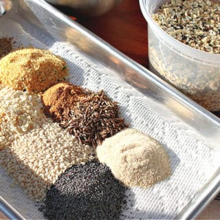 Everything seasoning blend on a small baking sheet with a container filled with it in the background.