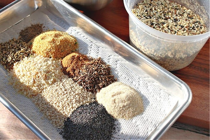 A small silver baking tray lined with a paper towel and piles of spices and seasoning for making homemade everything seasoning blend.