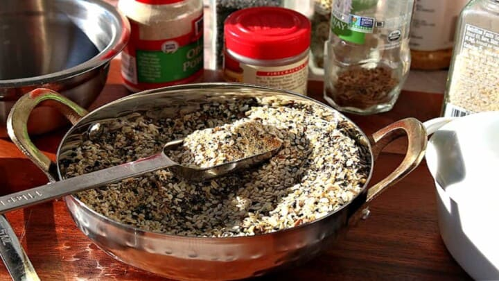 A shiny bowl filled with best everything seasoning blend along with a measuring spoon and jars of spices in the background