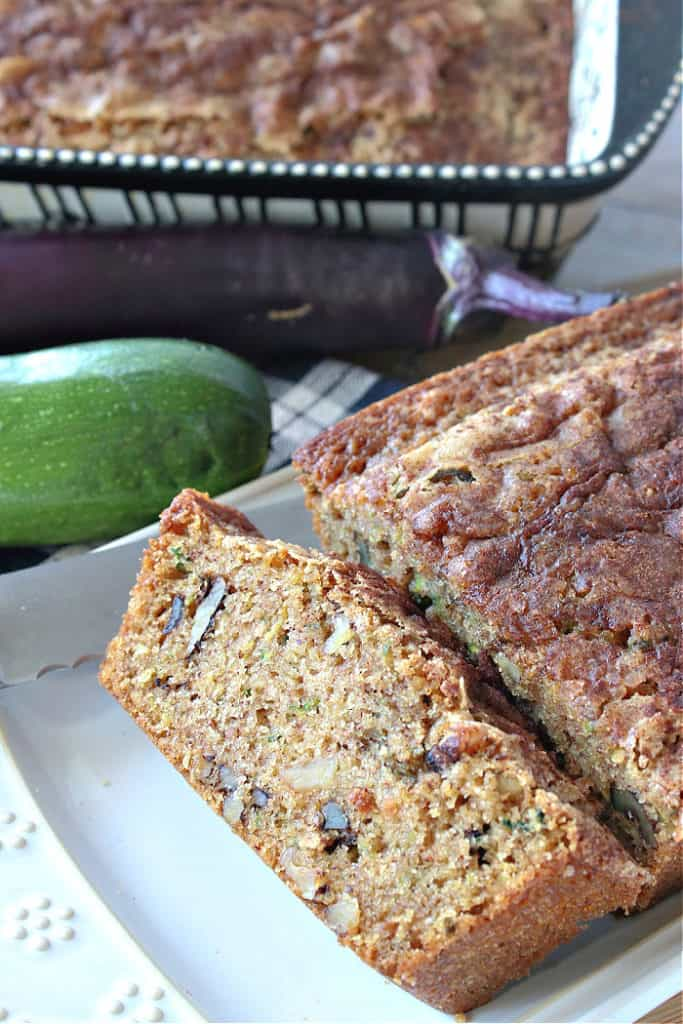 A vertical closeup of a sliced eggplant zucchini bread on a plate with a a whole loaf in a baking pan in the background.
