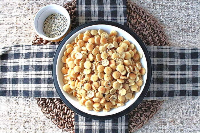 An overhead photo of a bowl of everything seasoned oyster crackers with a tan and black checkered napkin pattern under the bowl.