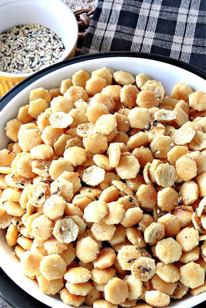 A closeup vertical overhead image of a bowl filled with everything seasoned oyster crackers with a small bowl of everything seasoning in the background.