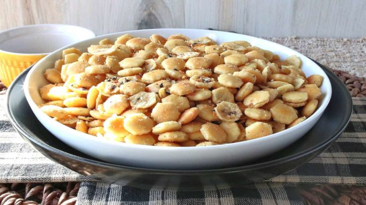 A bowl of everything oyster crackers on a black and tan checked tablecloth