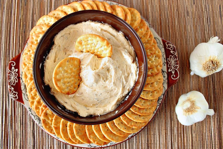An overhead photo of a brown bowl filled with roasted garlic dip on a platter surrounded by crackers and garlic bulbs on the side.