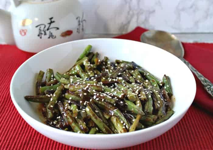 A white bowl of blistered green beans with miso and sesame on a red table cloth with a serving spoon.