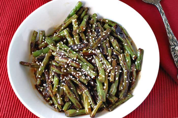 Overhead photo of a white bowl filled with blistered green beans with miso and sesame seeds on a red background.