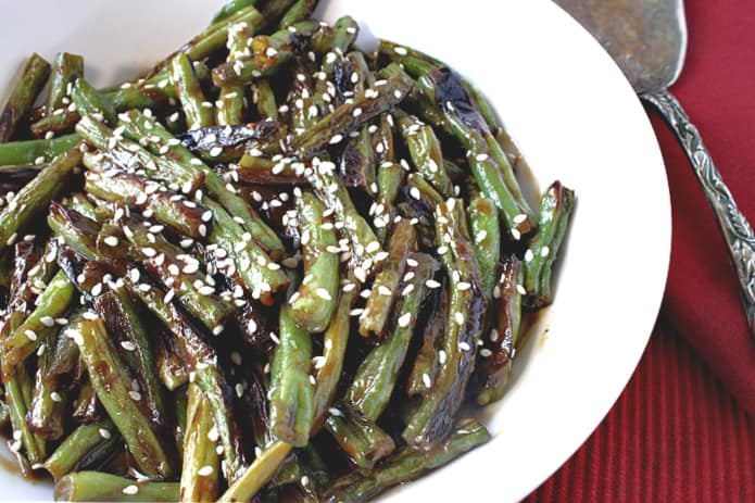 A closeup photo of blistered green beans with miso sauce and sesame seeds on a red tablecloth with a serving spoon on the side.